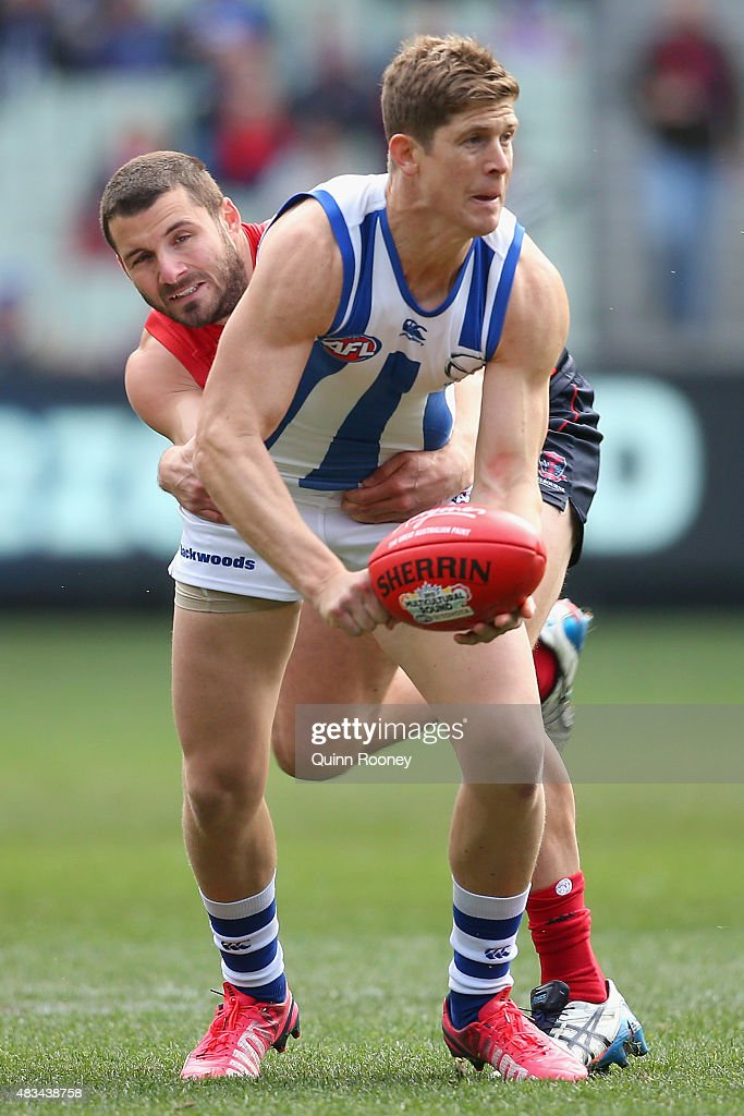 Nick Dal Santo of the Kangaroos handballs whilst being tackled by Colin Garland of the Demons during the round 19 AFL match between the Melbourne Demons and the North Melbourne Kangaroos at Melbourne Cricket Ground on August 9, 2015 in Melbourne, Australia.