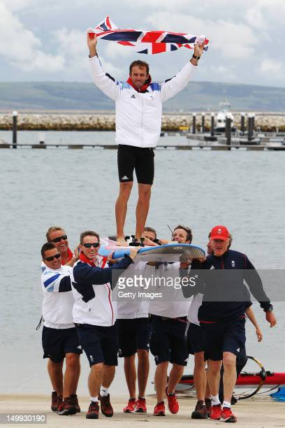 Nick Dempsey of Great Britain is carried onshore on his windsurf board by Team GB team mates after winning the silver medal in the RSX Men's Sailing...