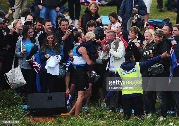 Nick Dempsey of Great Britain kisses his son ThomasFlynn as he swims onshore to the Nothe spectator area to greet friends and family after winning...