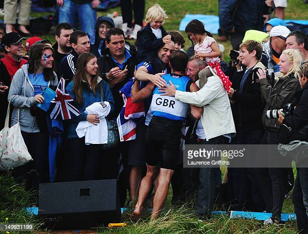 Nick Dempsey of Great Britain swims onshore to the Nothe spectator area to greet friends and family after winning silver in the Men's RSX Sailing on...