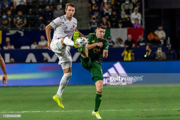 Nick DePuy of Los Angeles Galaxy battles Jaroslaw Niezgoda of Portland Timbers during the game at the Dignity Health Sports Park on October 16, 2021...