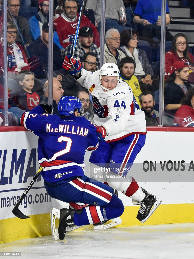 Nick Deslauriers #44 of the Laval Rocket hits Andrew MacWilliam #2 of the Rochester Americans against the boards during the AHL game at Place Bell on October 25, 2017 in Montreal, Laval, Canada. The Rochester Americans defeated the Laval Rocket 5-2.