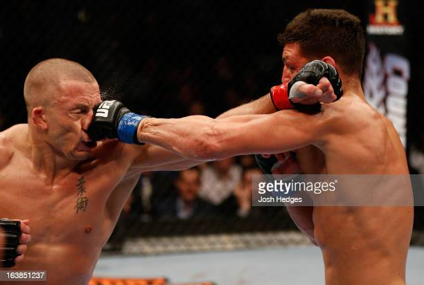 Nick Diaz punches Georges StPierre in their welterweight championship bout during the UFC 158 event at Bell Centre on March 16 2013 in Montreal...
