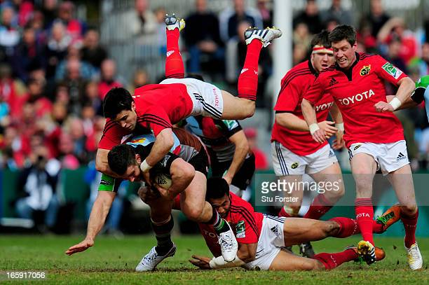 Nick Easter of Quins is hauled down by Conor Murray and Casey Laulala of Munster during the Heineken Cup quarter final match between Harlequins and...