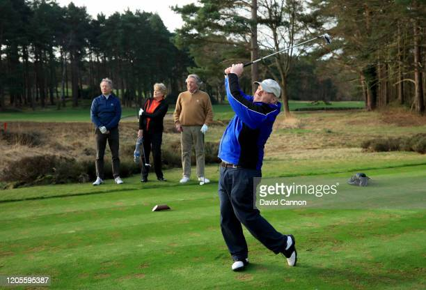Nick Edmund of England tees off on the fourth hole watched by his playing partners Paul Sedgwick the vice-captain of Sunningdale, Julia German the...