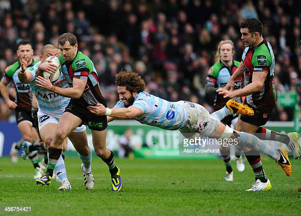 Nick Evans of Harlequins is tackled by Camille Gerondeau during the Heineken Cup Pool 4 round 4 match between Harlequins and Racing Metro 92 at The...
