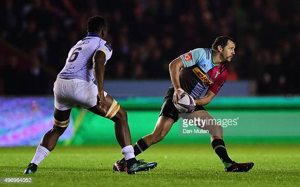 Nick Evans of Harlequins looks to offload under pressure from Fulgence Ouedraogo of Montpellier during the European Rugby Challenge Cup Pool 3 match...