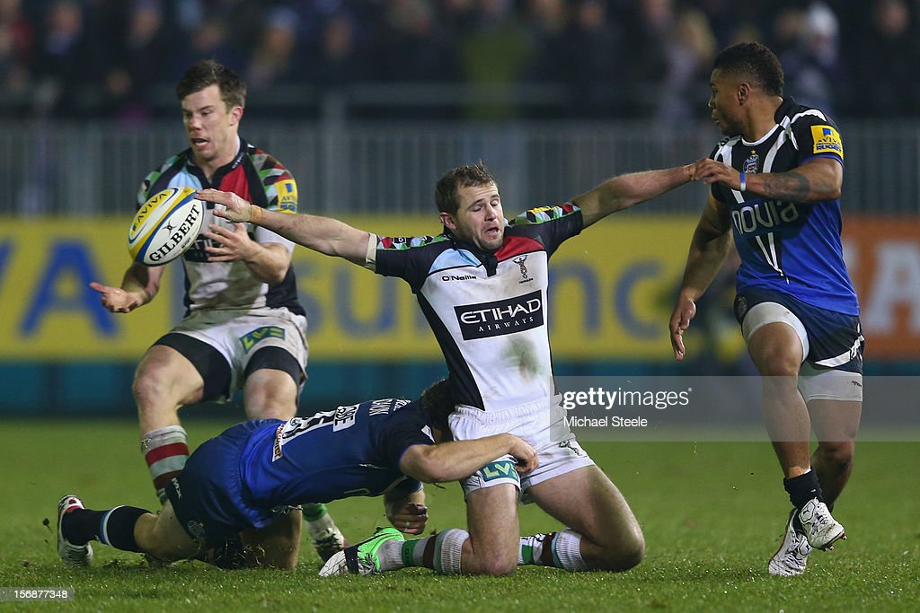 Nick Evans (C) of Harlequins manages to offload to Sam Smith (L) as Dave Attwood (2L) of Bath tackles and Kyle Eastmond (R) looks on during the Aviva Premiership match between Bath and Harlequins at the Recreation Ground on November 23, 2012 in Bath, England.