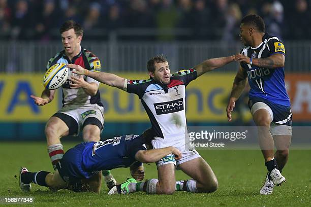 Nick Evans of Harlequins manages to offload to Sam Smith as Dave Attwood of Bath tackles and Kyle Eastmond looks on during the Aviva Premiership...