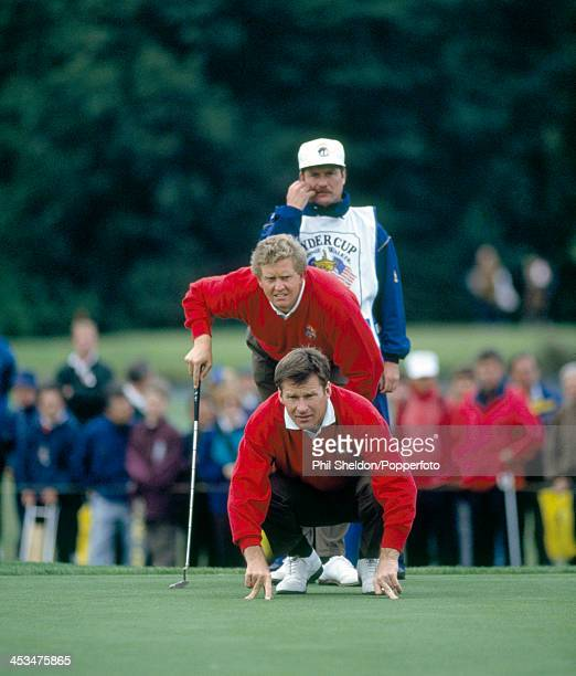 Nick Faldo and Colin Montgomerie of the European team lining up a putt with their caddie during the Ryder Cup golf competition held at The Belfry...