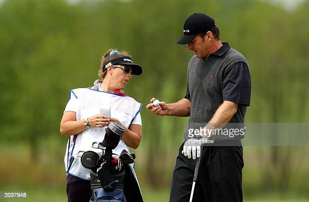 Nick Faldo of England and his caddy Fanny Sunesson of Sweden inspect a golf ball on the 8th hole during the third round of the SAP Deutsche Bank Open...