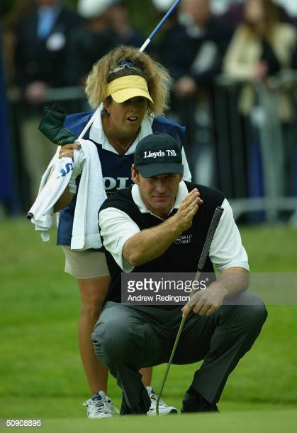Nick Faldo of England and his caddy Fanny Sunesson of Sweden line up a putt on the 18th hole during the third round of the Volvo PGA Championship at...