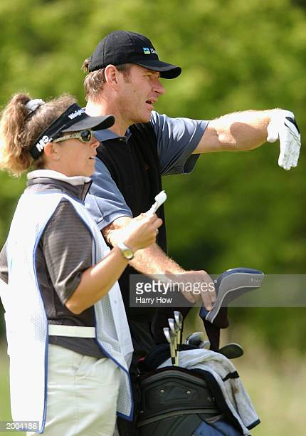 Nick Faldo of England discusses his shot with his caddie Fanny Sunesson on the 17th hole during the second round of the SAP Deutsche Bank Open on May...