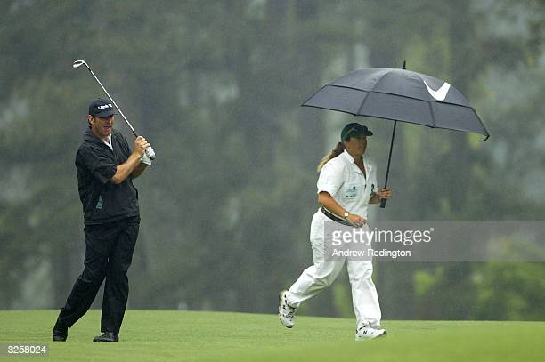Nick Faldo of England gets his caddie Fanny Sunesson Rogers to collect his divot during the first round of the Masters at the Augusta National Golf...