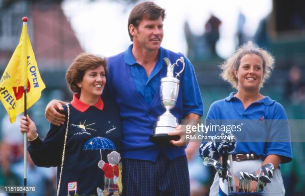 Nick Faldo of England holds the Claret Jug with wife Gill and caddie Fanny Sunesson following his victory during The 121st Open Championship held at...