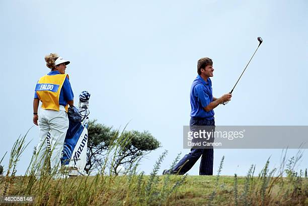 Nick Faldo of England plays his tee shot at the par 5 5th hole watched by his caddie Fanny Sunesson of Sweden during the 121st Open Championship at...