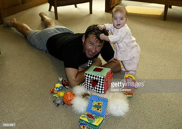 Nick Faldo of England plays with his baby daughter Emma at his hotel after the pro-am event prior to the Johnnie Walker Classic at the Alpine Golf...