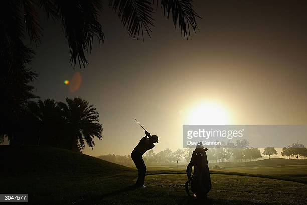 Nick Faldo of England practices against the early morning sun during the fog delay before the completion of the 2nd round of the Dubai Desert Classic...
