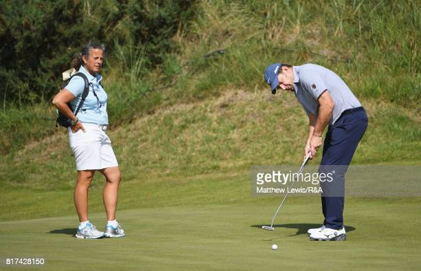 Nick Faldo of England putts watched by his former caddie Fanny Sunesson during a practice round prior to the 146th Open Championship at Royal...