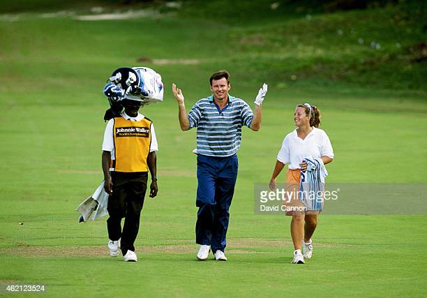 Nick Faldo of England using a local caddy to carry his bag in an unusual way as his regular caddy Fanny Sunesson of Sweden looks on as a preview for...