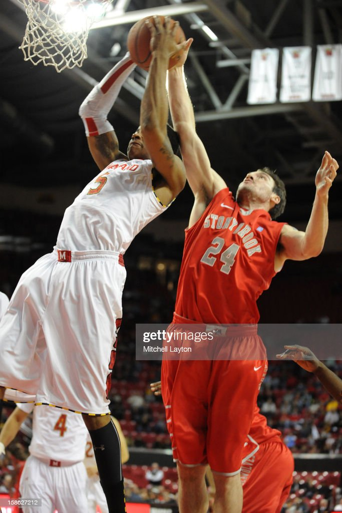 Nick Faust #5 of the Maryland Terrapins and Tommy Brenton #24 of the Stony Brook Seawolves fight for a rebound during a college basketball game on December 21, 2012 at the Comcast Center in College Park, Maryland.