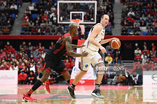 Nick Fazekas of the Kawasaki Brave Thunders handles the ball under pressure from Jawad Williams of the Alvark Tokyo during the BLeague match between...
