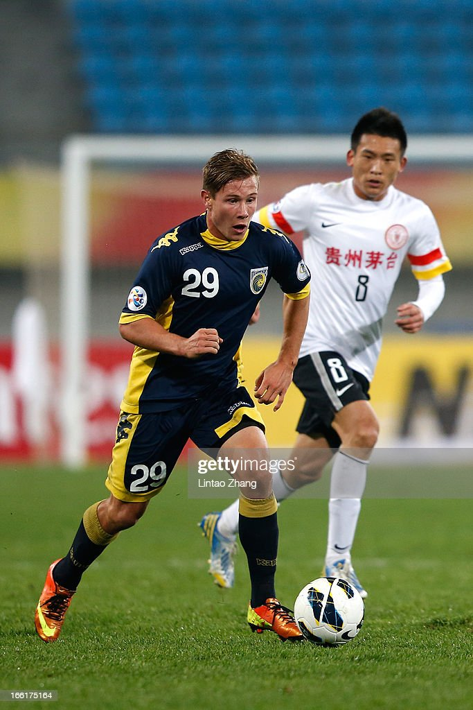 Nick Fitzgerald (L) of the Mariners challenges Li Chunyu of Guizhou Renhe during the AFC Champions League match between Guizhou Renhe and Central Coast Mariners at Olympic Sports Center on April 9, 2013 in Guiyang, China.