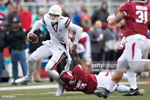 Nick Fitzgerald of the Mississippi State Bulldogs is tackled by De'Jon Harris of the Arkansas Razorbacks at Razorback Stadium on November 18 2017 in...
