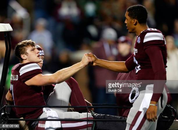 Nick Fitzgerald of the Mississippi State Bulldogs shakes hands with Keytaon Thompson as he is carted off the field during the first half of an NCAA...