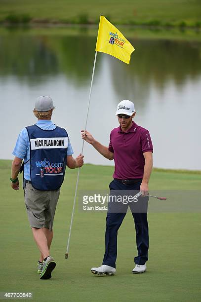 Nick Flanagan of Australia hands off a pin flag on the eighth hole during the first round of the Webcom Tour Chitimacha Louisiana Open presented by...