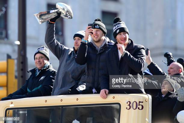 Nick Foles hoists the Vince Lombardi Trophy as team owner Jeffrey Lurie Nate Sudfeld and Carson Wentz of the Philadelphia Eagles ride on a parade...