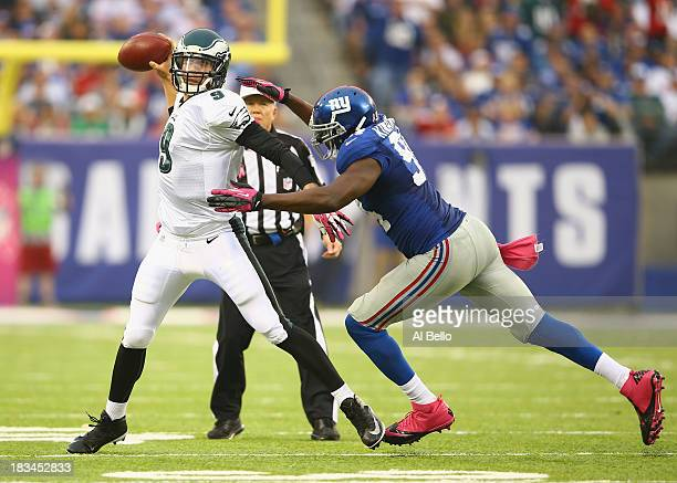 Nick Foles of the Philadelphia Eagles eludes Mathias Kiwanuka of the New York Giants during their game at MetLife Stadium on October 6 2013 in East...