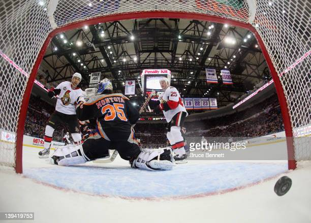 Nick Foligno and Chris Neil of the Ottawa Senators watch a shot by Chris Phillips enter the net in the second period against the New York Islanders...