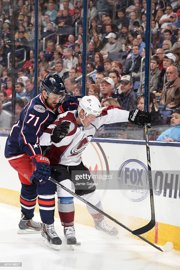 Nick Foligno #71 of the Columbus Blue Jackets and Tyson Barrie #4 of the Colorado Avalanche battle for the puck during the third period on April 1, 2014 at Nationwide Arena in Columbus, Ohio. Colorado defeated Columbus 3-2 in overtime.