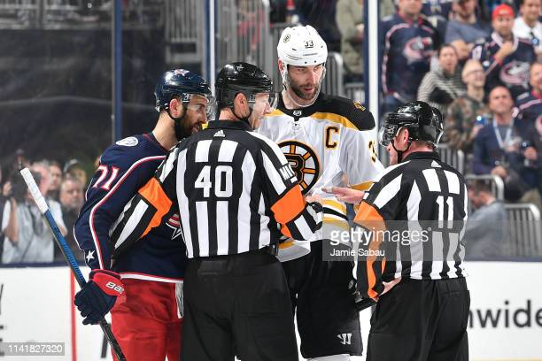 Nick Foligno of the Columbus Blue Jackets and Zdeno Chara of the Boston Bruins talk with referees Steve Kozari and Kelly Sutherland following a...