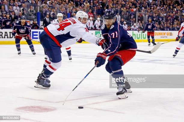 Nick Foligno of the Columbus Blue Jackets attempts to skate the puck past the defense of John Carlson of the Washington Capitals in Game Three of the...