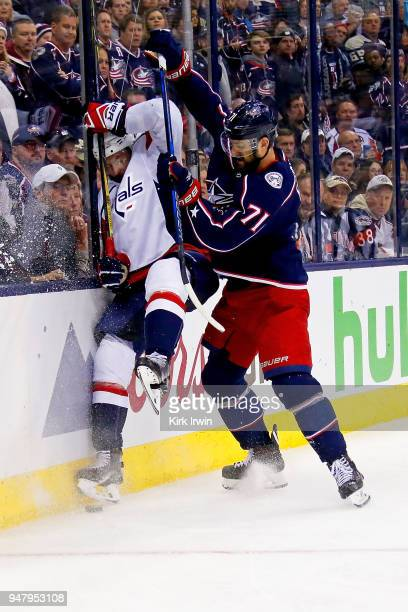 Nick Foligno of the Columbus Blue Jackets checks Michal Kempny of the Washington Capitals into the boards while chasing after a loose puck during the...