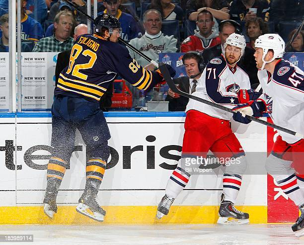 Nick Foligno of the Columbus Blue Jackets eludes a check from his brother Marcus Foligno of the Buffalo Sabres on October 10 2013 at the First...