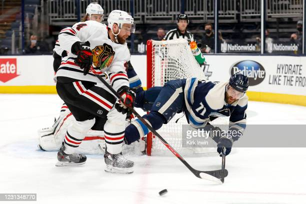 Nick Foligno of the Columbus Blue Jackets loses his footing while battling for control of the puck with Calvin de Haan of the Chicago Blackhawks...