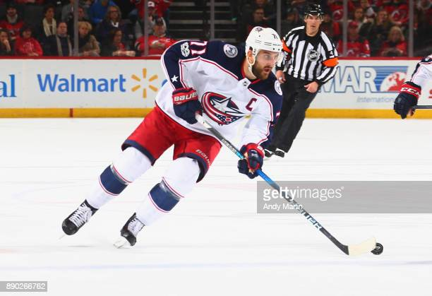 Nick Foligno of the Columbus Blue Jackets plays the puck during the game against the New Jersey Devils at Prudential Center on December 8 2017 in...