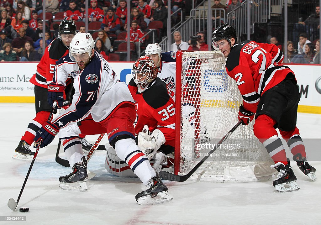 Nick Foligno #71 of the Columbus Blue Jackets reaches for the puck as Eric Gelinas #22 of the New Jersey Devils looks on during the third period at the Prudential Center on March 6, 2015 in Newark, New Jersey. The Blue Jackets defeated the Devils 3-2.