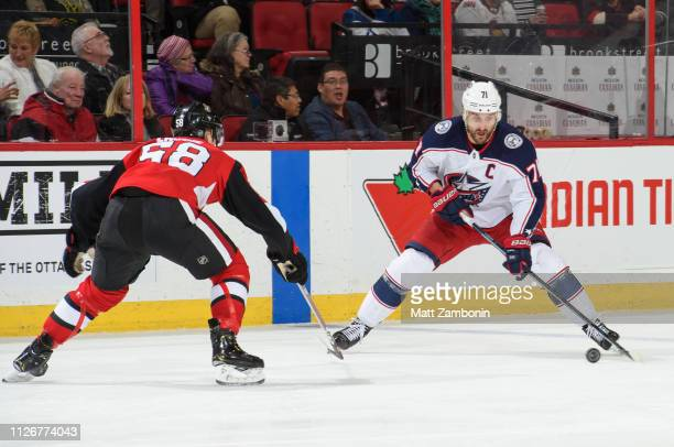 Nick Foligno of the Columbus Blue Jackets skates with the puck as Maxime Lajoie of the Ottawa Senators defends at Canadian Tire Centre on February 22...