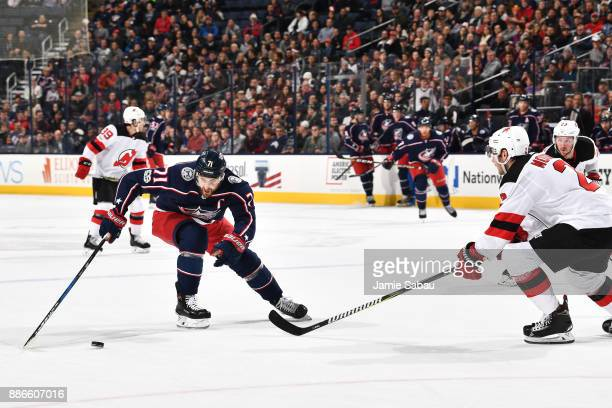 Nick Foligno of the Columbus Blue Jackets skates with the puck as John Moore of the New Jersey Devils defends during the first period of a game on...