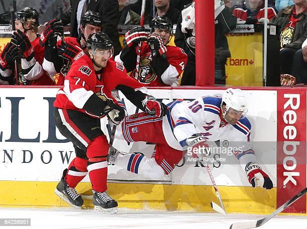 Nick Foligno of the Ottawa Senators bodychecks Nigel Dawes of the New York Rangers into the boards at Scotiabank Place on January 10, 2009 in Ottawa,...