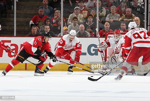 Nick Foligno of the Ottawa Senators drives the puck to the net against Brad Stuart and Chris Osgood of the Detroit Red Wings at Scotiabank Place on...