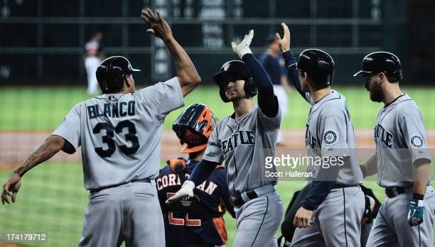Nick Franklin of the Seattle Mariners celebrates at home plate with his teammates after hitting a grand slam in the second inning against the Houston...