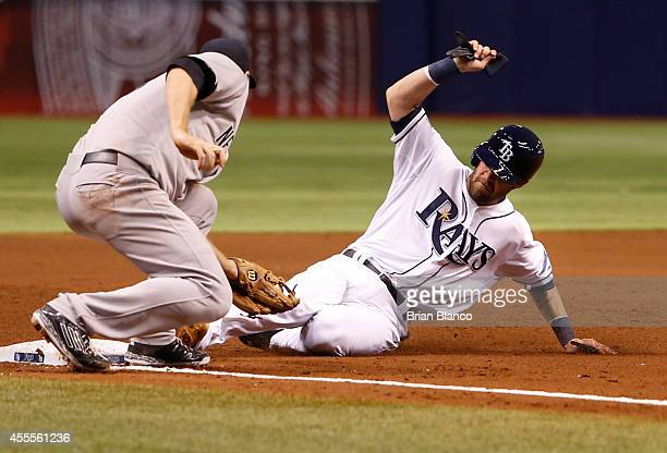 Nick Franklin of the Tampa Bay Rays slides safely into third base ahead of third baseman Chase Headley of the New York Yankees as he advances from...
