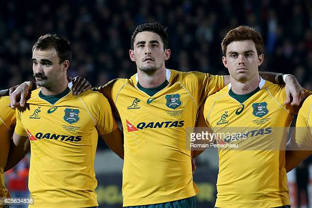 Nick Frisby Izaia Perese and Andrew Kellaway look on during the Australian anthem before the Test match between Barbarians and Australia on November...