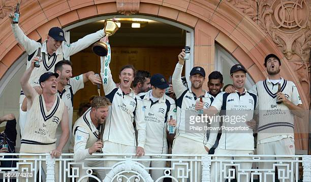 Nick Gubbins holds the trophy on the dressing room balcony after Middlesex won the county championship title on day four of the Specsavers County...