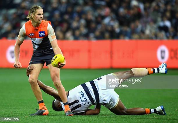 Nick Haynes of the Giants handballs whilst being tackled by Esava Ratugolea of the Cats during the round seven AFL match between the Geelong Cats and...
